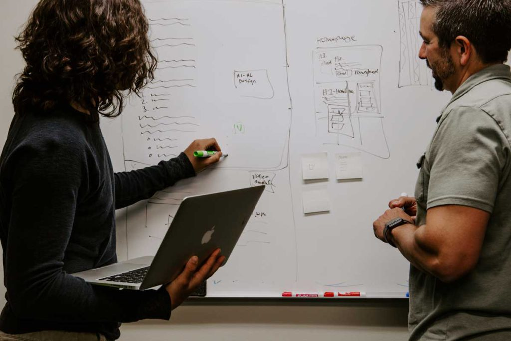 2 people discussing app prototype on board