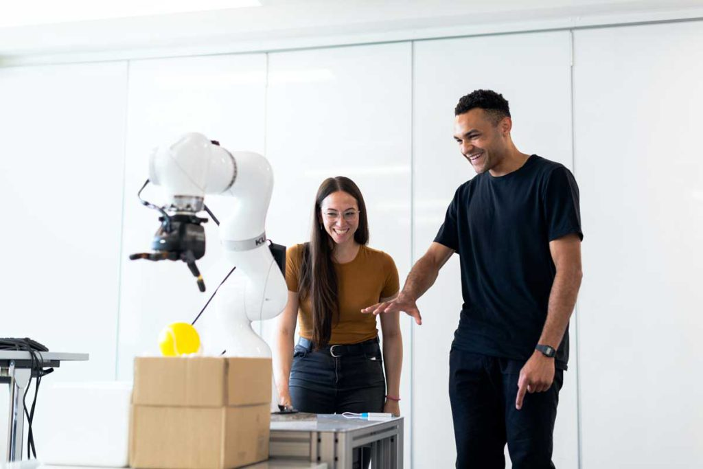 2 people playing with robot hand